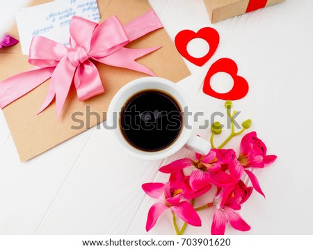 Coffee Cup, close pink gifts, letters and two hearts in the Cup, the concept of romance, love #703901620