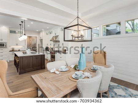 Dining Room and Kitchen Interior in New Luxury Home: Kitchen has Island, Sink, Cabinets, and Hardwood Floors. Dining Room has table with place settings. Pendant Lights accent Both Rooms #703934362