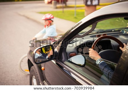 Accident. Small girl on the bicycle crosses the road in front of a car #703939984