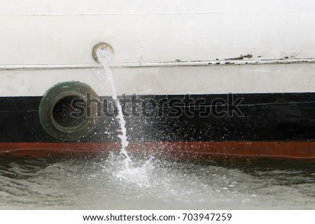 Water being pumped out the side of a small boat. A porthole is below and to the left of the pump hole. #703947259