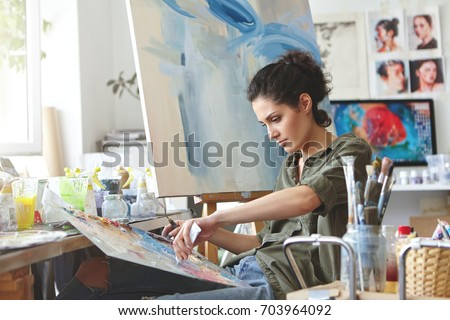Young female student having classes at art studio, learning how to draw landscapes, trying to mix different watercolors on cardboard. Concentrated woman with dark hair, dressed casually, painting Royalty-Free Stock Photo #703964092
