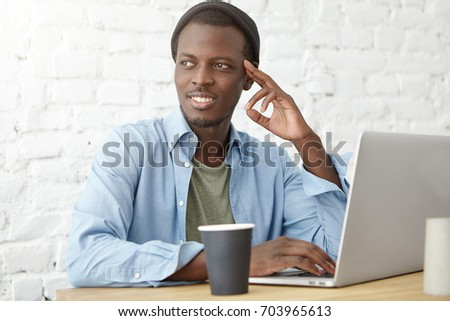 Sylish African American college student having coffee during lunch at cafeteria, using laptop while working on diploma project or preparing for classes. Young black hipster enjoying breakfast at cafe #703965613