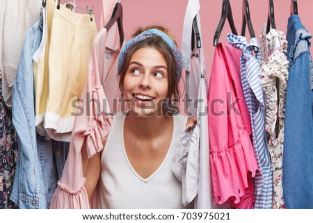 Cute female with dreamy expression looking through hangers with clothes, dreaming about new fashionable dress or blouse. Adorable woman daydreaming about going shopping with friends on weekend #703975021