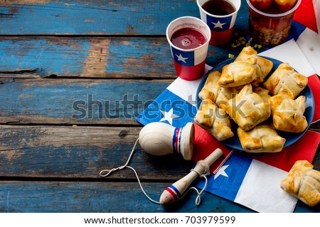 Chilean independence day concept. fiestas patrias. Chilean typical dish and drink on independence day party. Mini empanadas, mote con huesillo, wine with toasted flour chicha and tipical play emboque. #703979599