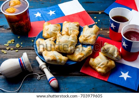 Chilean independence day concept. fiestas patrias. Chilean typical dish and drink on independence day party. Mini empanadas, mote con huesillo, wine with toasted flour chicha and tipical play emboque. #703979605