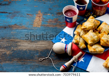 Chilean independence day concept. fiestas patrias. Chilean typical dish and drink on independence day party. Mini empanadas, mote con huesillo, wine with toasted flour chicha and tipical play emboque. #703979611