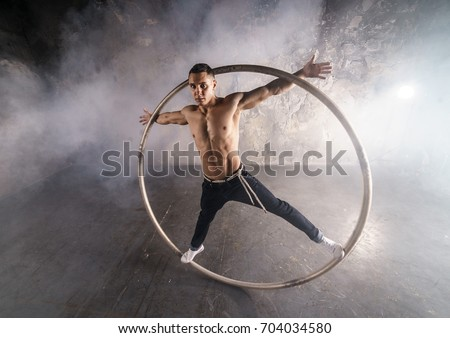Muscular circus performer spin in the big wheel  Royalty-Free Stock Photo #704034580