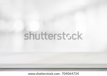 Empty white table top, counter, desk background over blur perspective bokeh light background, White marble stone table, shelf and blurred kitchen restaurant for food, product display mockup, template Royalty-Free Stock Photo #704064724