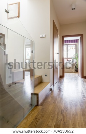 Corridor with glass panel in contemporary apartment with wooden floor #704130652