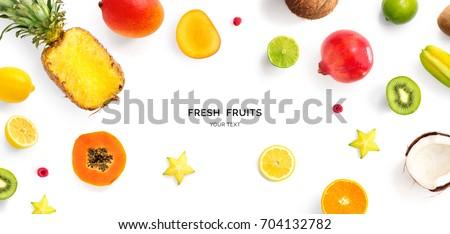 Creative layout made of pineapple, kiwi, lemon, lime, orange, papaya, coconut, pomegranate and carambola. Flat lay. Food concept. #704132782