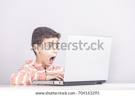 Little boy reacts after accidentally watching inappropriate content while surfing the internet. Internet safety and parental control concept #704163295