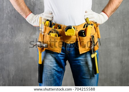 unknown handyman with hands on waist and tool belt with construction tools against grey background. DIY tools and manual work concept #704215588