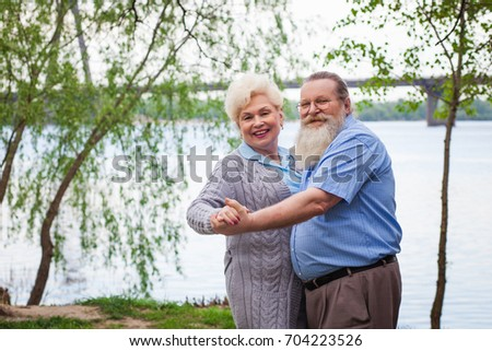 Elderly couple in love dancing on the background of the river in the park in the summer #704223526