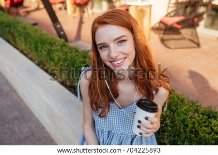 Close up of a young smiling redhead girl in earphones holding cup of coffee and looking at camera while sitting outdoors and listening to music #704225893