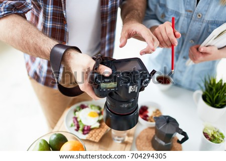 Close-up shot of hard-working food photographers looking through made photos on camera, served table for breakfast with fresh fruits, herbal tea, fried egg and lettuce