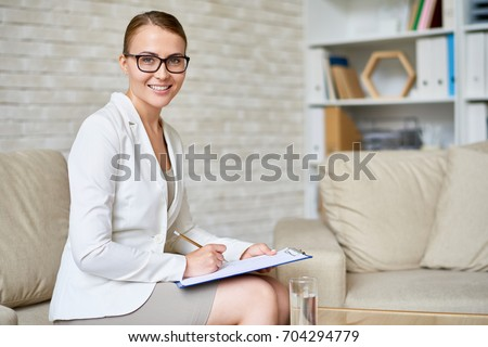Portrait of beautiful female psychologist wearing glasses posing with clipboard in therapy office smiling to camera Royalty-Free Stock Photo #704294779