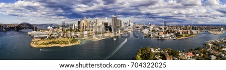 Wide aerial panorama of Sydney City architecture between the SYdney Harbour bridge and ANZAC bridge on a sunny day. Royalty-Free Stock Photo #704322025