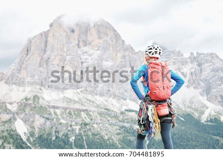 Female mountaineer with backpack, helmet and harness with climbing gear enjoying stunning view to mount Tofana di Rozes before ascent during summer day in Dolomite Alps - adventure concept #704481895