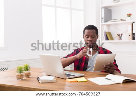 African-american businessman in office, reading news on tablet, drinking coffee #704509327