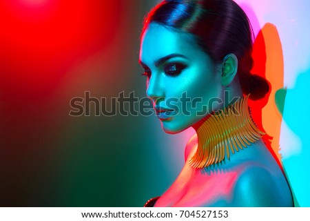 High Fashion model woman in colorful bright lights posing, portrait of beautiful sexy girl with trendy make-up. Art design, colorful make up. Over colourful vivid background. Night club dancer #704527153