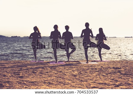 Silhouette of  yoga group of people doing tree pose and namaste with calm relax emotion at beach,Meditation pose,Wellness and Healthy Lifestyle. #704533537
