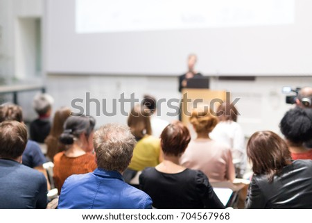 Business and entrepreneurship symposium. Female speaker giving a talk at business meeting. Audience in conference hall. Rear view of unrecognized participant in audience. Copy space on whitescreen. #704567968
