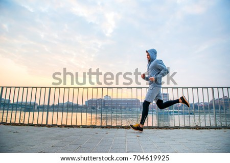 A handsome young man running in the sunset next to a fence on the riverside Royalty-Free Stock Photo #704619925