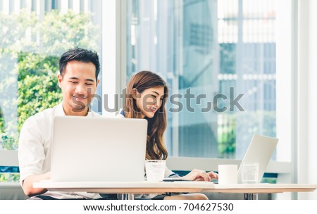 Young Asian couple or college student using laptop computer notebook work together at coffee shop or university campus. Information technology, cafe lifestyle, office meeting, or e-learning concept #704627530