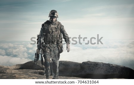 soldier with a rifle. Steps against clouds. #704631064