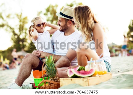 Happy family is enjoying beach and having pic-nic.