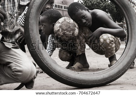 local kids on a street pose for my picture with ball and tire