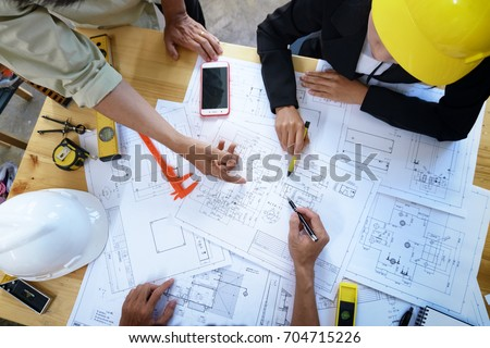 engineer people meeting working and pointing at a drawings in office for discussing. Engineering tools and construction concept. #704715226