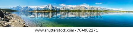 Grand Teton National Park, Wyoming.  Panorama showing reflection of mountains on Jackson Lake near Yellowstone. #704802271