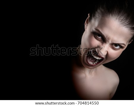 angry nude girl screaming at camera on black background with copy space #704814550