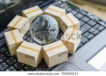 International freight or shipping service for online shopping or ecommerce concept : Paper boxes or carton put in circle around a clear crystal globe with world map on a computer notebook keyboard. #704890213