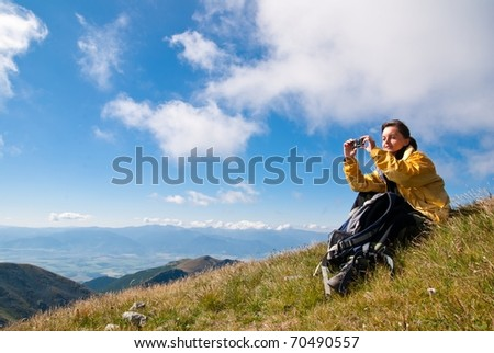 Young person relaxes on hiking in mountains and taking photo with mobile phone