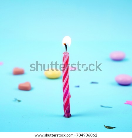 Colorful candle illumination with decoration on sky blue background