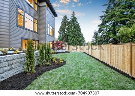 Luxurious contemporary three-story wood siding home exterior in Bellevue. Nice backyard landscape with well kept lawn, flower beds and wooden fence. Northwest, USA Royalty-Free Stock Photo #704907307