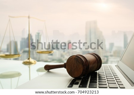 law legal technology concept.  judge gavel on computer with scales of justice on desk of lawyer. #704923213