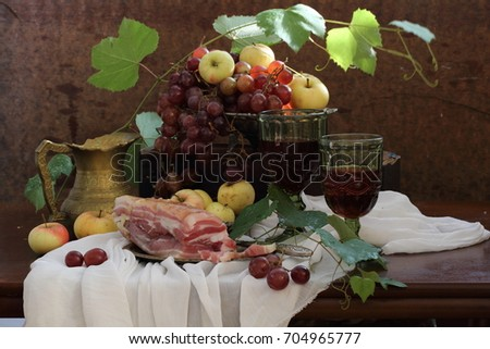 Still life with wine, grapes and salty bacon on a wooden table  #704965777