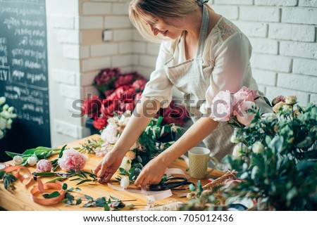 Small business. Male florist unfocused in flower shop. Floral design studio, making decorations and arrangements. Flowers delivery, creating order #705012436