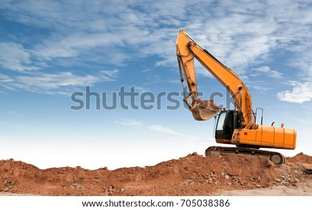 An articulated wheel crawler loader or dozer on mound in the industrial building construction site #705038386