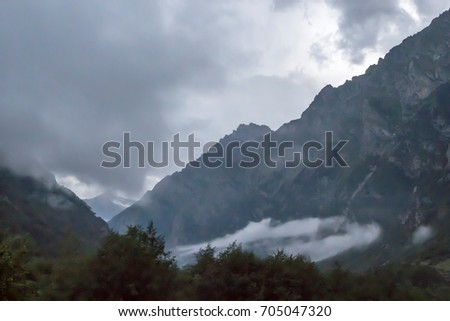 Mountain landscape. Cloudy weather in the picturesque gorge, fog in mountains, white clouds. Nature of the North Caucasus #705047320