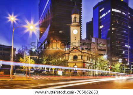 Historic heritage North Sydney post office building with clock tower against tall modern business high-rises at sunset on car traffic street. Royalty-Free Stock Photo #705062650