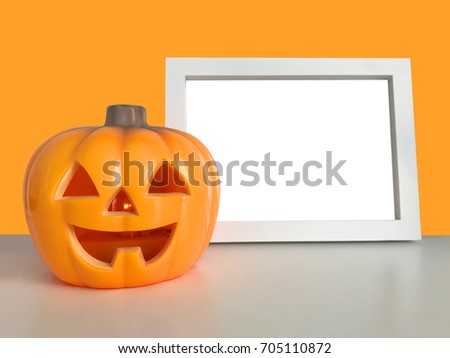 Happy Halloween orange background. Pumpkin toy smiling face. Plastic Jack o lantern light. Horizontal white photo frame mock up template on the table. Empty space. Trick or treat. Holiday sign symbol.