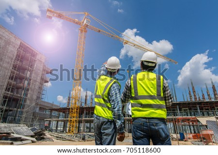 Civil engineer checking work with walkie-talkie for communication to management team in the construction site #705118600