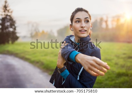 Woman stretching at park while listening to music. Young woman working out at sunset. Healthy sport girl doing stretching exercise early in the morning at park. #705175810