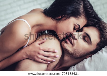 Happy couple is lying in bed together. Enjoying the company of each other. #705188431