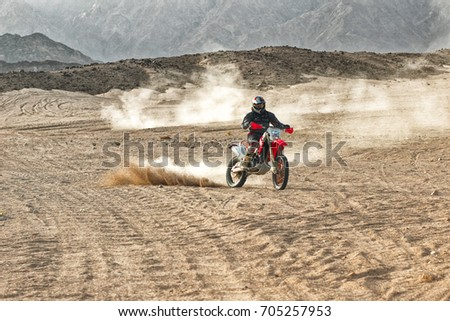 Off road biker wearing helmet driving in desert lifting white thin sand up. Hot summer day in Egypt. Warm colored sand & mountains background. Extreme sports & hobbies