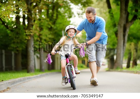 Happy father teaching his little daughter to ride a bicycle. Child learning to ride a bike. Family activities at summer. #705349147